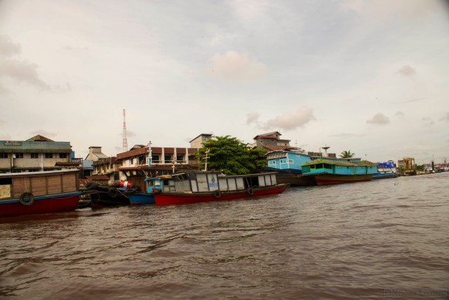 Boats and buildings line the riverside in Pontianak